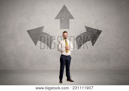 Charming businessman in doubt, choosing from three directions in front of a grey wall