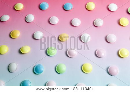 Flying Saucer Multi Coloured Candy Sweets On A Gradient Background Pink And Blue. Minimal Color Stil