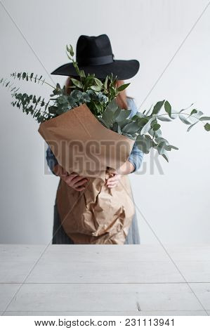 Girl In A Hat With A Bouquet Of Eucalyptus In Hands. Girl Florist Holding Eucalyptus