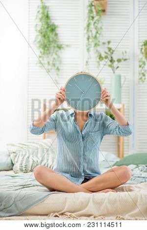 Portrait Of A Young Woman With Alarm Clock Sitting In The Beautiful And Bright Bedroom With Green Pl