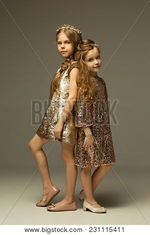 The Fashion Portrait Of Young Beautiful Teen Girls In Gold Dress At Studio. The Beauty, Fashion, Glo