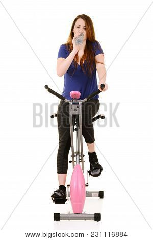 Woman Drinking Water During Cardio On An Exercise Bike