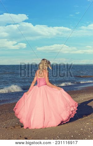 Woman In Pink Tulle Dress Walking On The Beach