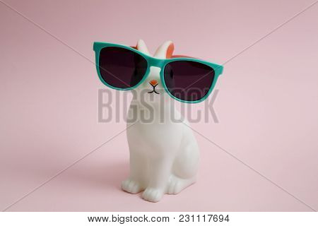A Cute White Plastic Bunny Wearing Adhesive Eye Doll On A Pink Background. Minimal Color Still Life