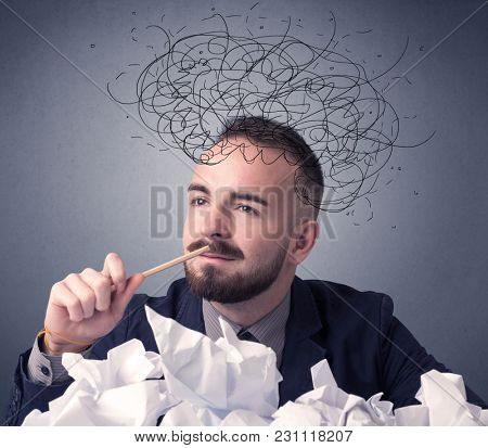 Young businessman sitting behind crumpled paper with scribbles over his head