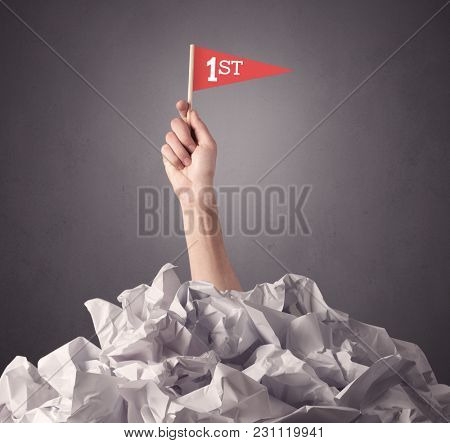 Female hand emerging from crumpled paper pile holding a red flag with first written on it