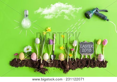 Easter Flower Bed Garden With Row Of Painted Eggs Amongst Flowers, Clouds, Light Bulb As The Sun, An