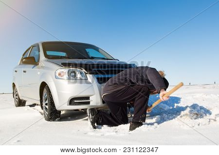 The Driver Digs Out The Car With A Shovel From The Snow.