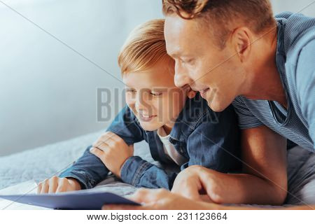 New Knowledge. Positive Nice Smart Man Lying On The Bed And Talking To His Son While Sharing His Exp