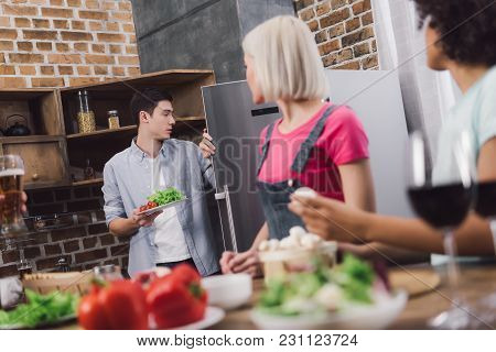 Man Taking Vegetables From Fridge In Kitchen