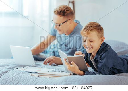 Young Businessman. Delighted Positive Nice Boy Lying On The Bed And Taking Notes While Learning To B