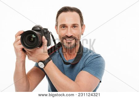 Portrait of a happy mature man dressed in t-shirt holding photo camera isolated over white background