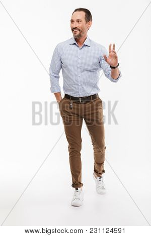 Full length portrait of a cheerful mature man dressed in shirt walking and waving his hand isolated over white background