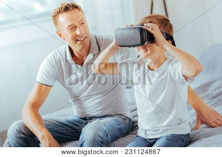 New Dimension. Delighted Happy Positive Boy Sitting On The Bed With His Father And Wearing Virtual R