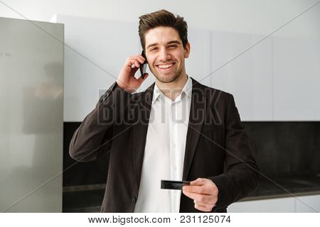 Photo of happy young businessman standing in home indoors. Looking camera talking by mobile phone holding credit card.
