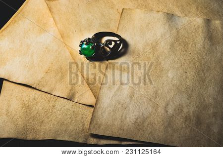 Ring With Shinny Green Gem And Ancient Parchment
