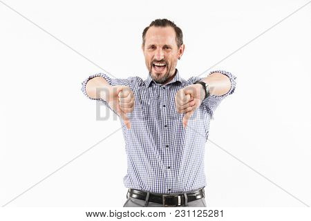 Image of displeased adult man isolated over white background. Looking camera showing thumbs down.