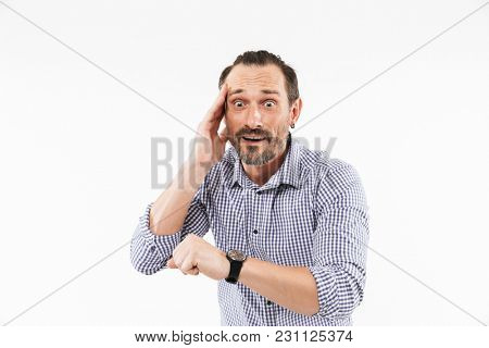 Photo of shocked adult man isolated over white background. Looking at watch scared.