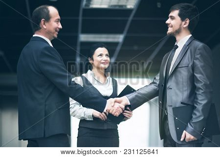 The Image Of A Business Team Discussing Latest Financial Results And Fixing The Deal With A Handshak