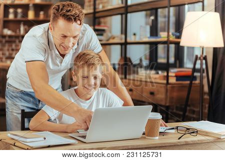 Look Here. Nice Positive Handsome Man Standing Behind His Son And Pointing At The Laptop Screen Whil