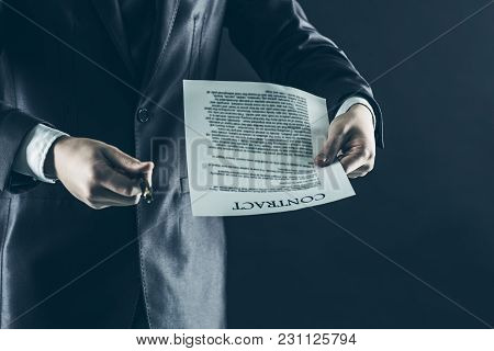 Businessman Holding A Pen And A Document With The Terms Of The Contract.photo On A Black Background