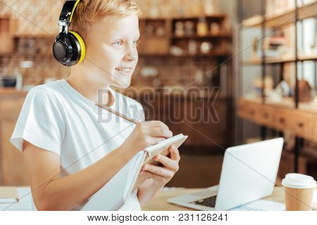 Sudden Inspiration. Joyful Happy Positive Boy Wearing Headphones And Taking Notes While Listening To