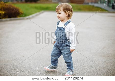 Cute Baby Girl With Blonde Hair Running Outdoors. Little Girl 1-2 Year Old.