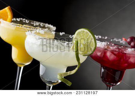 Lime Margarita, Orange Margarita And Cherry Margarita Cocktail Mix In Salt Rimmed Glasses Garnished