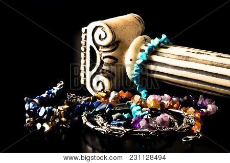 Colorful Bracelets Made Of Natural Stones And Antique Column On Black Background