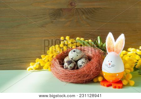 Easter Background. Easter Bunny And Eggs In The Nest Near The Mimosa Flowers. Easter Background. Eas