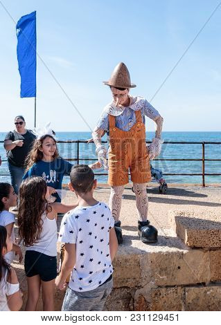 Caesarea, Israel, March 03, 2018 :  Visitors Of The Purim Festival Touch The Participant Dressed In