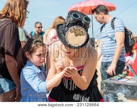 The Participant Of The Purim Festival Dressed In Fabulous Costume, Puts A Drawing On The Girl's Hand