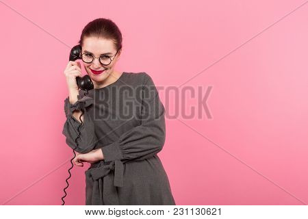 Portrait Of Serious Businesswoman With Hair Bun In Formal Dress And Eyeglasses Talks On Vintage Phon