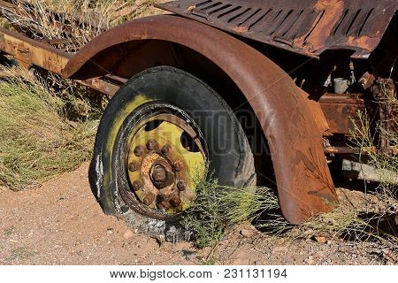 A Rotten Tire Partially Rests On A Truck Rim With 10 Lug Nuts Attached To The Chassis.