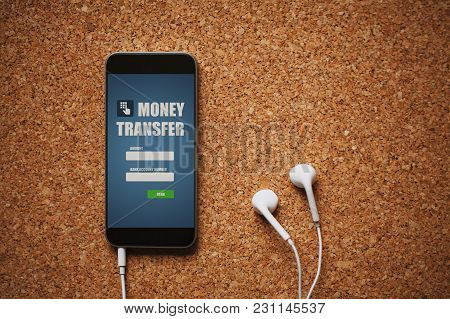 Mobile Phone With Money Transfer App In The Screen, White Earphones, And Copy Space, On A Cork Panel