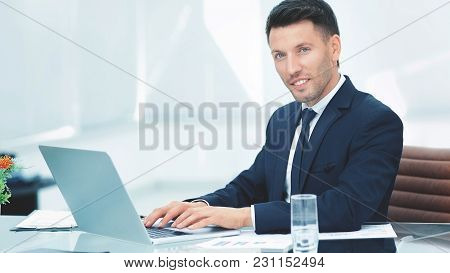 Businessman In Black Business Suit Sitting Behind A Desk In The Spacious Office And Working On Lapto