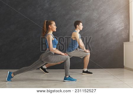Fitness Couple Warmup Stretching Training At Gray Background Indoors. Young Man And Woman Making Aer