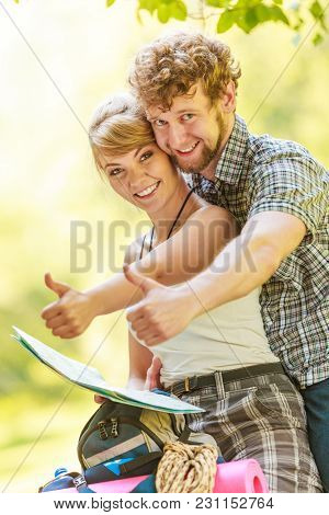 Man And Woman Tourists Backpackers Reading Map On Trip While Resting. Young Couple Hikers Searching