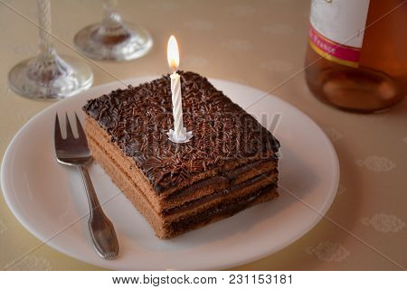 Close Up Of A Slice Of A Layered Chocolate Cake With One Candle And Two Glasses And Bottle Of Wine