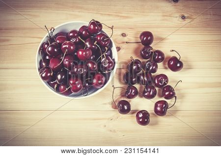 Fresh Ripe Cherries Berries In White Bowl On Wooden Background. Top View.