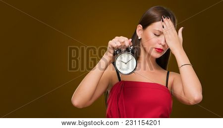 Tired Woman Holding Alarm Clock against a dark yellow background