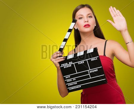 Young Woman Holding Clapper Board against a yellow background