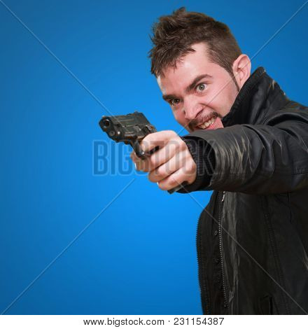 angry man pointing with gun against a blue background