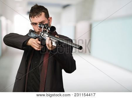 Young Man Aiming With Rifle at a building