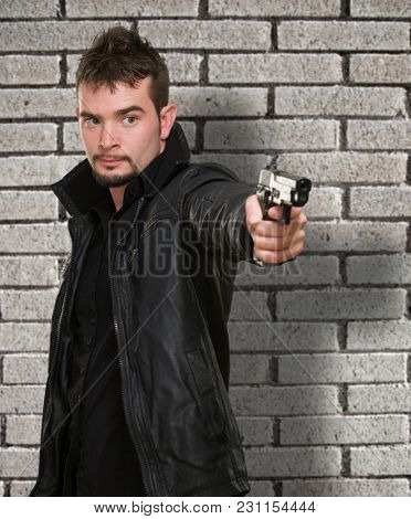 handsome man pointing with gun against a brick wall