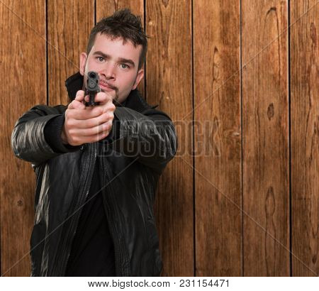 portrait of a man pointing with a gun against a wooden background