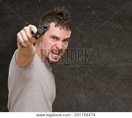 furious man pointing with gun against a grunge background