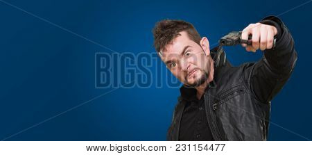 furious man pointing with a gun against a blue background