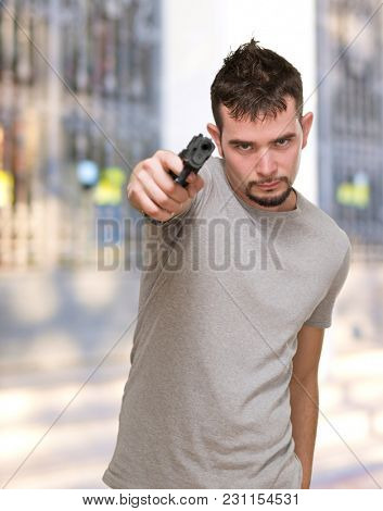 mad man pointing with gun in front of a building