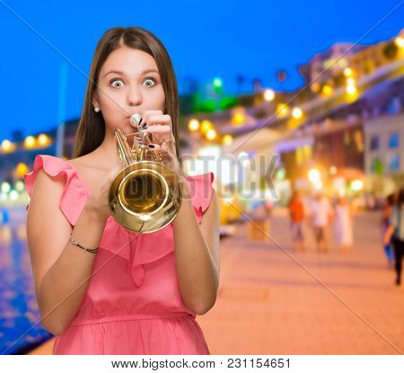 Young Woman Blowing Trumpet by a port at night